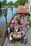Leute, die heraus durch den Flussufer im Sonnenschein essen Stockfoto