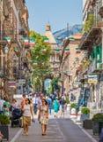 Leute, die herein über Vittorio Emanuele in Palermo mit Porta Nuova im Hintergrund gehen Sizilien, Italien lizenzfreies stockfoto