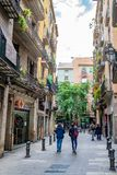 Leute, die hinunter schmale Stra?e zwischen Gesch?fte/Speicher in Barcelona gehen lizenzfreie stockbilder