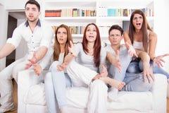 Leute, die ihr Lieblingsteam aufpassen, im Fernsehen zu verlieren lizenzfreie stockbilder