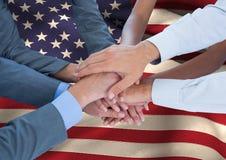 Leute, die ihre Hände auf eine amerikanische Flagge zusammenfügen Stockfotografie