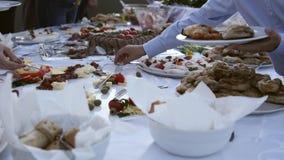 Leute, die ihre Platten mit Lebensmittel an einem schwedischen Tisch füllen stock video