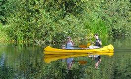 Leute, die im Kanu auf dem Fluss Ouse in Cambridgeshire schaufeln Stockfotos