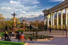 Leute, die im Park mit Ansichten der Berge sich entspannen stockfotografie