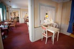 Leute, die innerhalb des alten Restaurants, mit Weinlesemöbeln und gemütlichen Räumen des historischen Hauses frühstücken Lizenzfreie Stockbilder