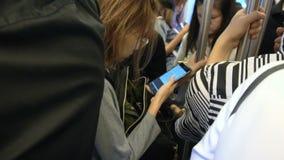 Leute, die intelligente Telefone beim Austauschen in der U-Bahn in gedrängtem Zug, Bangkok, Thailand - 20. April 2017 verwenden stock footage