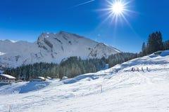Leute, die in Klewenalp-Skiort in den Schweizer Alpen Ski fahren und sledging Stockfotos