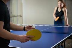 Leute, die Klingeln pong Tennis am Turnhallenraum spielen stockbilder