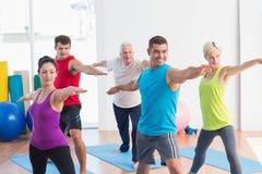 Leute, die Kriegershaltung in der Yogaklasse tun lizenzfreies stockfoto
