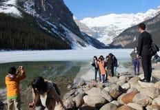 Leute, die Lake Louise und Berge ansehen Stockfotografie