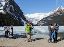 Leute, die Lake Louise und Berge mit Jetcontrail ansehen Lizenzfreie Stockfotos
