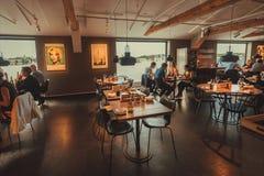 Leute, die Lebensmittel im Restaurant mit Wasseransicht, in die kulturelle Mitte Fotografiska essen stockbild