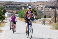 Leute, die mit dem Fahrrad in der Stadt in den Milos, Griechenland fahren Viel tou Lizenzfreie Stockfotografie