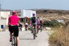 Leute, die mit dem Fahrrad in der Stadt in den Milos, Griechenland fahren Viel tou Lizenzfreies Stockbild