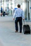 Leute, die mit Gepäck im Flughafen gehen Stockbilder