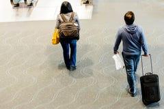 Leute, die mit Gepäck im Flughafen gehen Stockbild