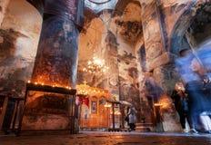 Leute, die mit Kerzen im dunklen Innenraum der Kirche der Erzengel mit Freskos beten Stockfoto
