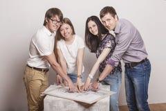 Leute, die mit Zeichnungen auf dem Tisch arbeiten Lizenzfreie Stockfotografie