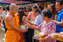 Leute, die morgens klebrigen Reis Mönchen anbieten Lizenzfreie Stockfotografie