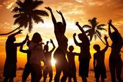 Leute, die Partei durch den Strand genießen Lizenzfreies Stockbild
