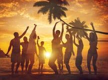 Leute, die Partei durch den Strand genießen Stockfotos