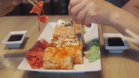 Leute, die Rollen in Japan-Restaurant oder -Sushi-Bar essen stock footage