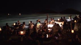 Leute, die Seeufercafé im im Freien nachts sich entspannen stock video