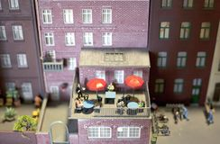 Leute, die Sommer auf einem Balkon in einer Miniaturwelteinrichtung genießen Lizenzfreies Stockbild