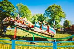Leute, die Spaß auf Achterbahn im Park haben Lizenzfreie Stockbilder