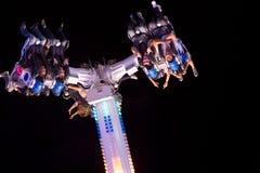 Leute, die Spaß in einer Achterbahn nachts haben Lizenzfreie Stockfotografie