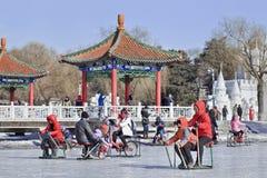 Leute, die Spaß mit dem Sledging auf Eis in Nanhu-Park, Changchun, China haben Lizenzfreie Stockbilder
