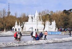 Leute, die Spaß mit dem Sledging auf Eis in Nanhu-Park, Changchun, China haben Lizenzfreies Stockfoto