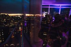 Leute, die Spaß, sprechend haben und wirken auf Stadtereignis oder Darstellung auf der Dachspitze nachts aufeinander ein Lizenzfreie Stockbilder