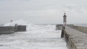 Leute, die stürmischen Ozean am Wellenbrecherpier mit Leuchtturm aufpassen stock video footage