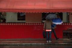 Leute, die in die Stadt am bewölkten Tag mit Regen gehen stockfotos