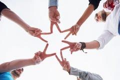 Leute, die Sternform mit ihren Fingern bilden Stockbild