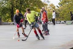 Leute, die Straßenhockey mit Stöcken und Rollen spielen lizenzfreie stockfotografie