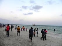 Leute, die am Strand in dem Indischen Ozean Mombasa gehen Stockbilder