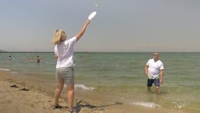 Leute, die Strand-Tennis durch die Küste spielen stock footage