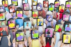 Leute, die Tabletten vor den Gesichtern halten Stockbilder