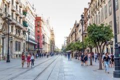 Leute, die tagsüber in eine Fußgängerstraße nahe Kathedrale in Sevilla, Spanien gehen Berühmter Grenzstein lizenzfreie stockfotos