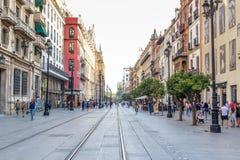 Leute, die tagsüber in eine Fußgängerstraße nahe Kathedrale in Sevilla, Spanien gehen Berühmter Grenzstein stockfotos