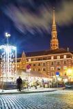 Leute, die um Quadrat mit künstlerischem Weihnachtsbaum in Riga schlendern Lizenzfreies Stockbild