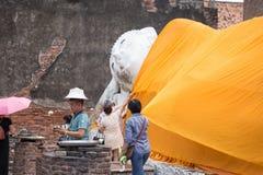 Leute, die um Statue Schlafens Buddha beten Lizenzfreie Stockfotografie