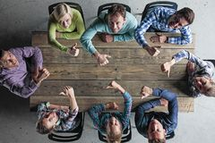 Leute, die um Tabelle mit den Daumen oben sitzen lizenzfreies stockfoto