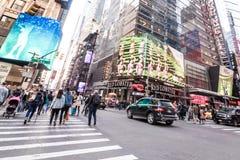 Leute, die um Times Square-Gebäude in New York City, twillight gehen Lizenzfreie Stockbilder