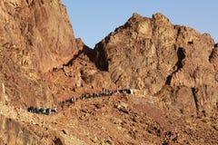 Leute, die unten den Berg steigen Stockfoto