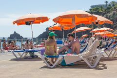 Leute, die unter einem Sonnenschirm an einem allgemeinen Schwimmenbad bei Madeira, Portugal sitzen Stockbild