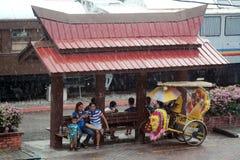 Leute, die vom Regen an der Bushaltestelle entgehen Lizenzfreies Stockbild