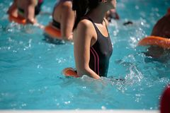 Leute, die Wasser-Aerobic in einem Swimmingpool im Freien tun Lizenzfreie Stockbilder